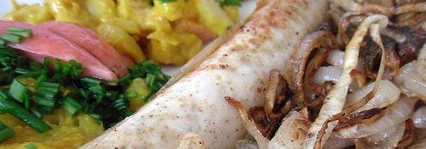 Der Kartoffelsalat mit Radieschen-Kimchi auf dem Teller - mit einer Bratwurst und Röstzwiebeln